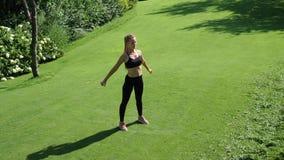 Ung kvinna som övar, för sträckning och för utbildning squatting utomhus Sunt kondition, wellnesslivsstil Sport som är cardio lager videofilmer
