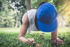 Ung kvinna som övar genomkörarekondition som utanför gör plank på royaltyfria bilder