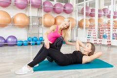 Ung kvinna som övar med hennes konditioninstruktör Royaltyfria Foton