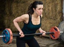 Ung kvinna som övar med vikter Arkivfoto