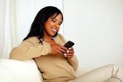 Ung kvinna som överför ett meddelande vid mobiltelefonen Arkivfoto