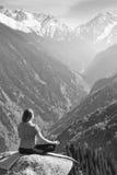 Ung kvinna som överst mediterar av berg Royaltyfri Bild