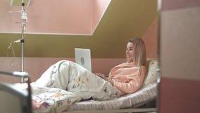 Ung kvinna som använder bärbara datorn som har video pratstund på sjukhussäng Fotografering för Bildbyråer