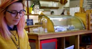 Ung kvinna som använder bärbara datorn i kafét 4k arkivfilmer