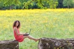Ung kvinna som använder bärbara datorn i natur Arkivfoton