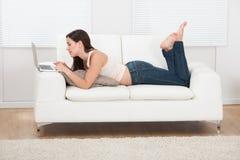 Ung kvinna som använder bärbara datorn, medan ligga på soffan Royaltyfria Bilder