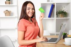 Ung kvinna som använder bärbara datorn, medan rymma kreditkorten Royaltyfri Fotografi