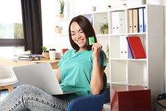 Ung kvinna som använder bärbara datorn, medan rymma kreditkorten Arkivfoton