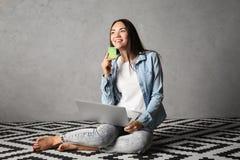 Ung kvinna som använder bärbara datorn, medan rymma kreditkorten Royaltyfri Foto