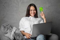 Ung kvinna som använder bärbara datorn, medan rymma kreditkorten Royaltyfri Bild