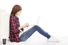 Ung kvinna som använder bärbara datorn och sitter på golvet Arkivbilder