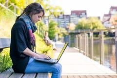 Ung kvinna som använder bärbara datorn på en flodstrand fotografering för bildbyråer