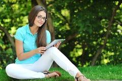 Ung kvinna som använder den digitala minnestavlan Royaltyfria Bilder