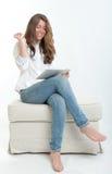 Ung kvinna som använder den digitala minnestavlan Royaltyfri Fotografi