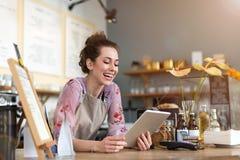 Ung kvinna som använder den digitala minnestavlan i coffee shop royaltyfri fotografi