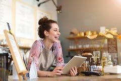 Ung kvinna som använder den digitala minnestavlan i coffee shop royaltyfri foto
