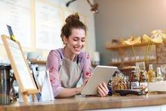 Ung kvinna som använder den digitala minnestavlan i coffee shop fotografering för bildbyråer