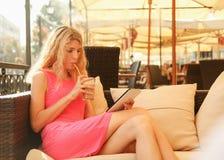 Ung kvinna som använder den digitala minnestavlan i kafé Royaltyfria Bilder