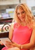 Ung kvinna som använder den digitala minnestavlan i kafé Arkivbilder