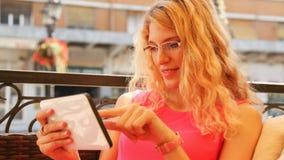 Ung kvinna som använder den digitala minnestavlan i kafé Arkivbild