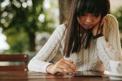 Ung kvinna som använder den digitala minnestavlan på coffeeshop Royaltyfria Foton