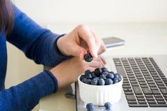 Ung kvinna som använder den hemmastadda bärbar datordatoren och äter blåbäret Arkivbilder