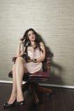 Ung kvinna som använder den nostalgiska telefonen, medan sitta på stol mot texturerad bakgrund Royaltyfria Bilder