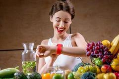 Ung kvinna som använder den smarta klockan i köket Fotografering för Bildbyråer