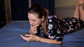 Ung kvinna som använder den smarta telefonen för cell Lycklig kvinna som ler att ligga på säng i sovrum lager videofilmer