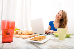 Ung kvinna som använder en bärbar datordator som har after frukosten Royaltyfria Bilder