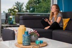 Ung kvinna som använder en fjärrkontroll på soffan royaltyfria bilder