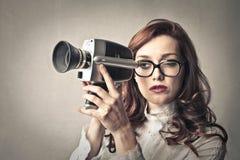 Ung kvinna som använder en kamera arkivbild