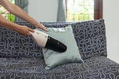 Ung kvinna som använder en liten manuell dammsugare, medan göra ren kudden på soffan royaltyfri fotografi