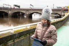 Ung kvinna som använder en minnestavla, medan gå royaltyfria bilder