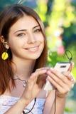 Ung kvinna som använder en smartphone för att lyssna till musik Fotografering för Bildbyråer