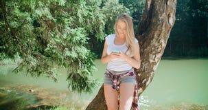 Ung kvinna som använder en smartphone i en skog Fotografering för Bildbyråer