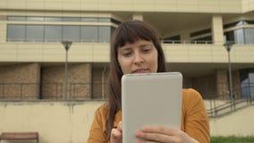 Ung kvinna som använder ett minnestavlaanseende på bakgrunden av en kontorsbyggnad arkivfilmer