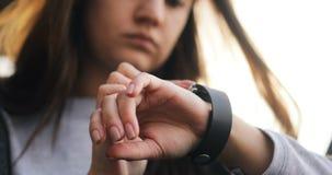 Ung kvinna som använder hennes apparat för teknologi för smartwatchpekskärm wearable Att försöka för ung kvinna som är nytt, ilar lager videofilmer