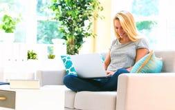 Ung kvinna som använder hennes bärbar dator in på hennes soffa arkivfoto