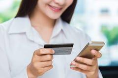 Ung kvinna som använder hennes kreditkort för att göra direktanslutet att inhandla thro Arkivfoto