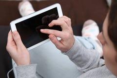 Ung kvinna som använder hennes minnestavladator Arkivfoto
