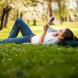 Ung kvinna som använder hennes minnestavladator, medan koppla av utomhus Royaltyfri Bild