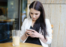 Ung kvinna som använder hennes mobiltelefon i ett utomhus- kafé Royaltyfri Fotografi