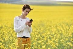 Ung kvinna som använder hennes smarta telefon i det fria Arkivbilder