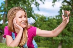 Ung kvinna som använder hennes smarta telefon på parkera Fotografering för Bildbyråer