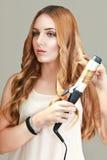 Ung kvinna som använder krullande järn på hennes hår royaltyfria foton