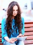 Ung kvinna som använder minnestavlan Royaltyfri Foto