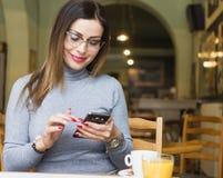 Ung kvinna som använder mobiltelefonen i coffee shop royaltyfri foto