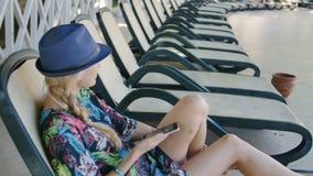 Ung kvinna som använder mobiltelefonen, medan ligga på sunbed på hotellet stock video