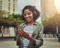Ung kvinna som använder mobiltelefonen, medan lyssna med hörlurar på hennes huvud arkivfoton